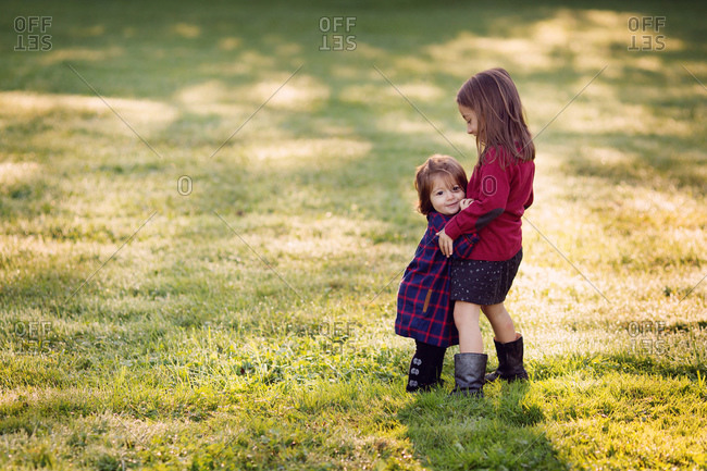 A girl hugs her little sister