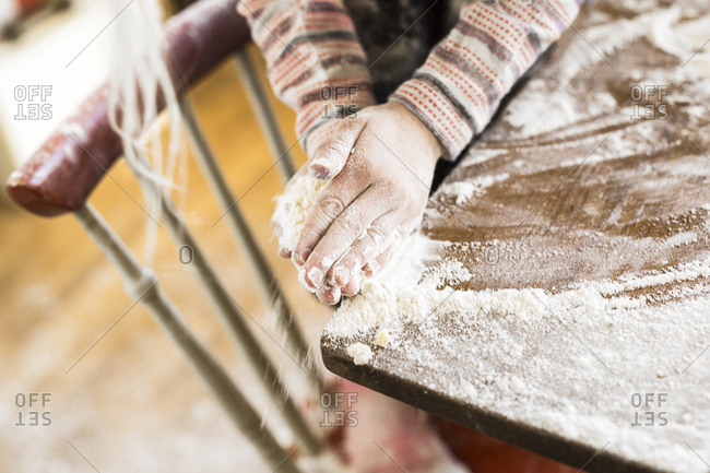 Child wiping off flour on a table