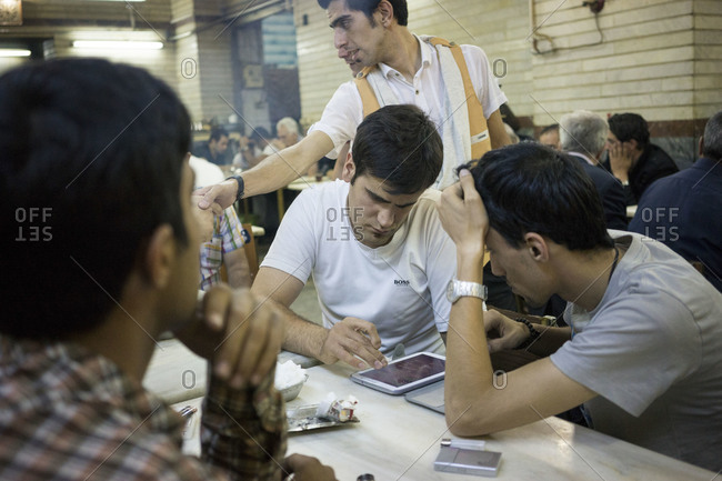 Tabriz, Iran - June 7, 2014: Iranian youths play backgammon on a tablet in a traditional cafe  in Tabriz