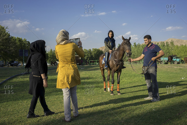 Tehran, Iran - June 13, 2014: A young woman poses on a horse