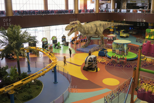 Shiraz, Iran - June 29, 2014: A few children play at an amusement park built inside a large shopping mall located in the outskirts of Shiraz, Iran