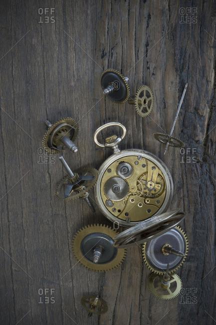 Old pocket watch and cogwheels on dark wood