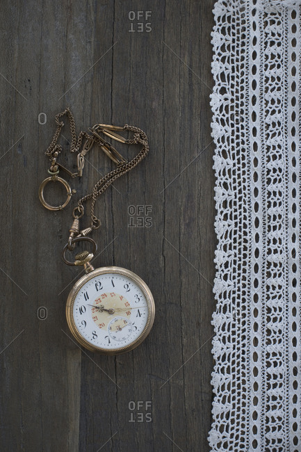 Old pocket watch and lace on dark wood