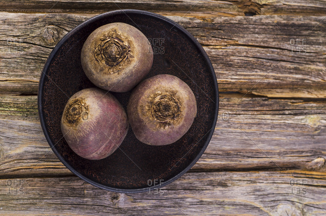 Bowl with three beetroots on wood