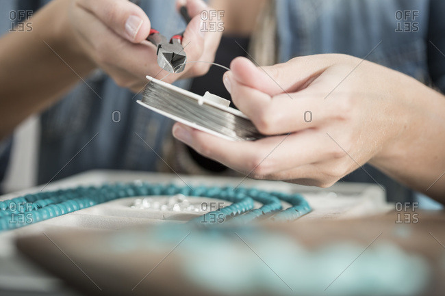 Close-up of woman working with pliers to create a bead necklace