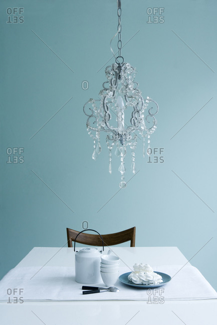 Chandelier hanging above a table
