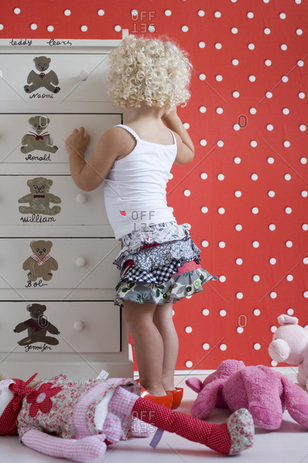 Blonde girl standing at a drawer