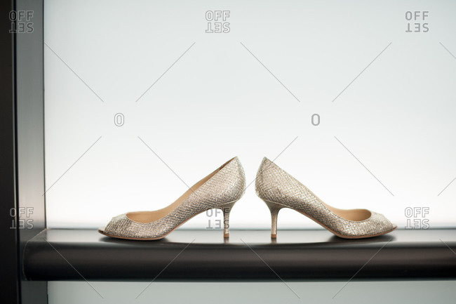 Pair of women's silver heels on a black shelf