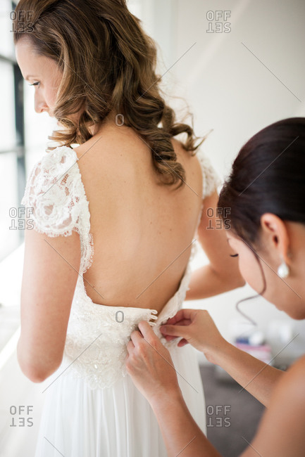 Woman helping bride get dressed in her gown
