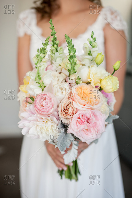 Bride holding her bouquet of white, pink, and yellow flowers