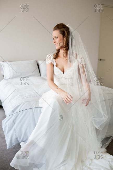 Bride sitting on bed in her gown and veil