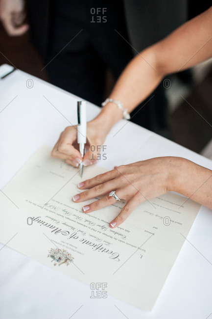Close-up of bride's hands signing a Certificate of Marriage