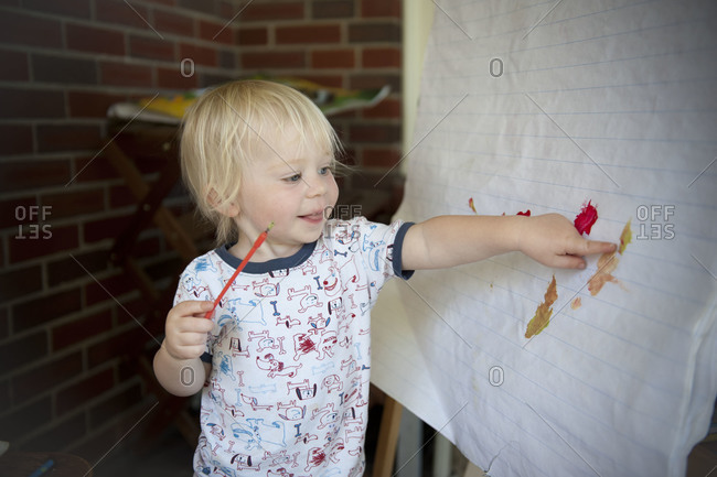 A little boy proudly shows off his artwork