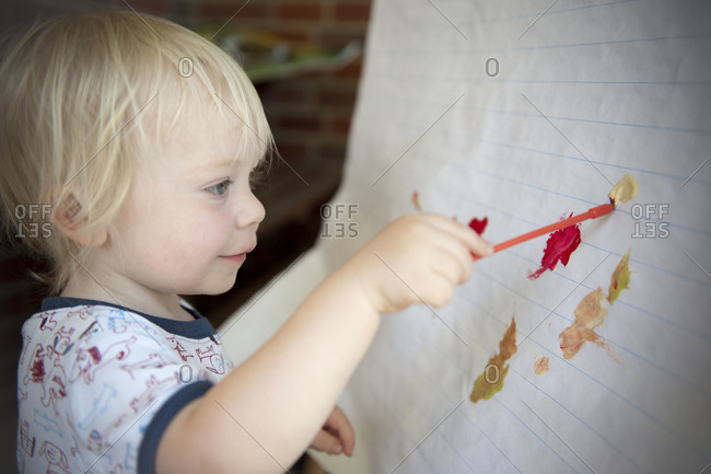A little boy painting at an easel