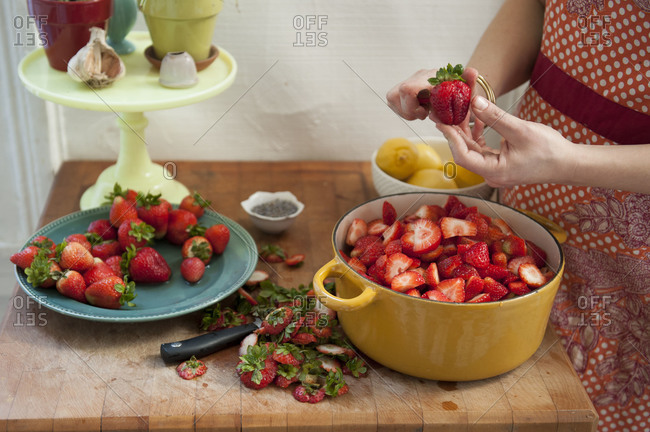 A woman hulling strawberries over a big bowl