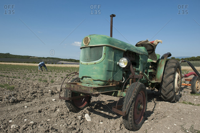 An old tractor in field with farmer working in the background