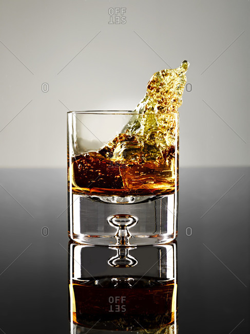 Whiskey splashing out of a glass
