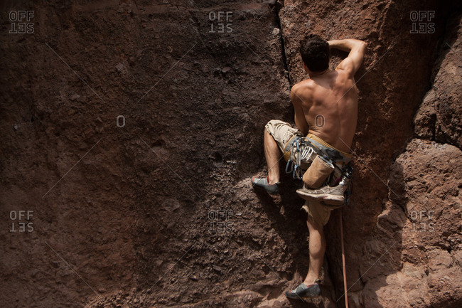 Shirtless man climbing on a cliff in Pinnacles National Monument, USA
