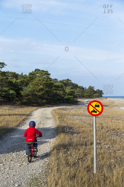 Boy on bicycle on dirt path