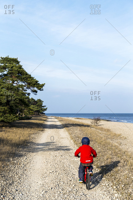 Boy on bicycle on dirt road