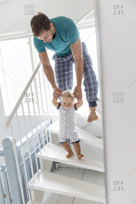 Father teaching son to walk downstairs