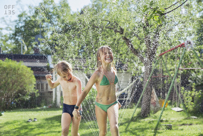 Girl and boy playing with water in backyard