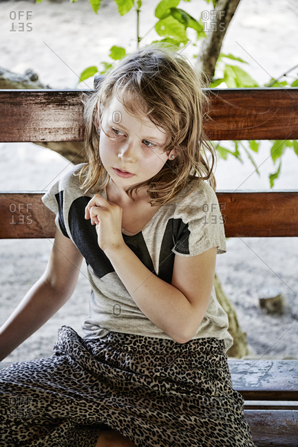 Girl looking away sitting on a bench