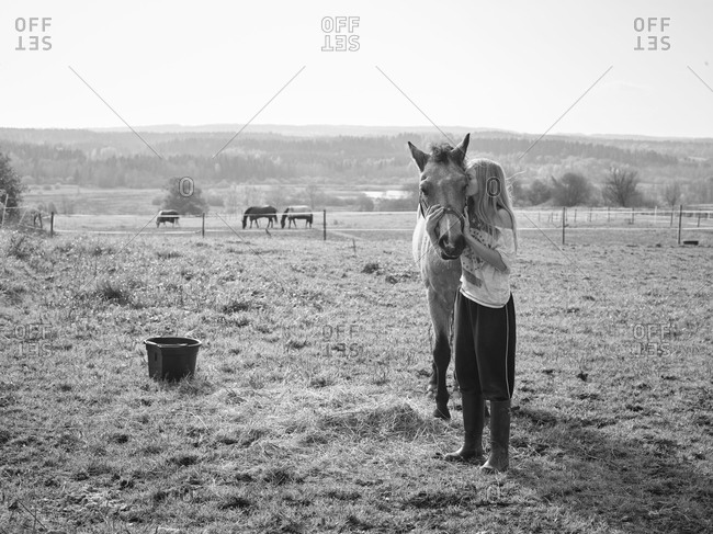Girl with horse on pasture
