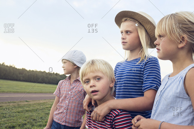 Group of blond children standing at the side of the world
