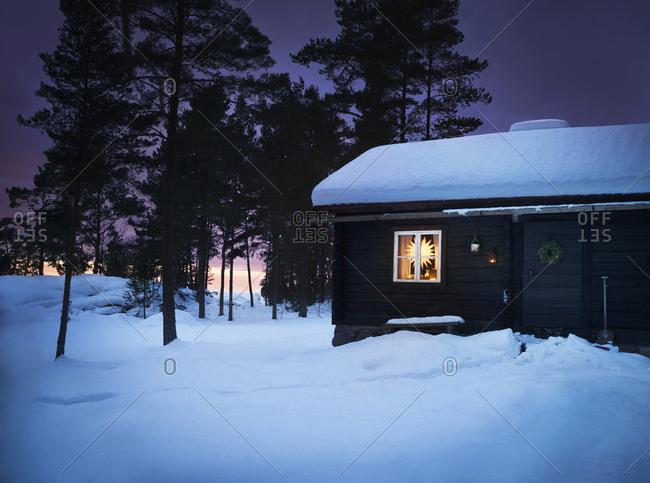 Illuminated wooden house at dusk