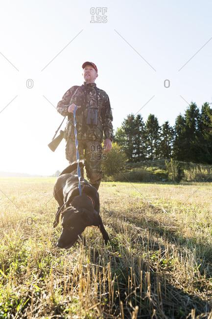 Man hunting with black lab