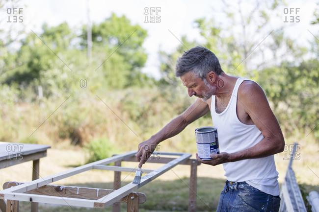 Mature man painting window