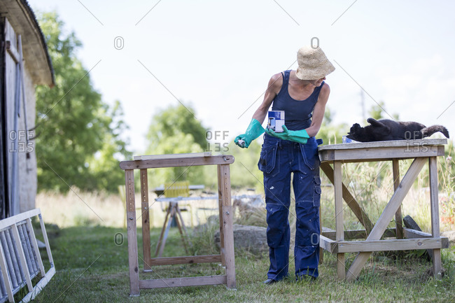 Mature woman looking at cat while painting