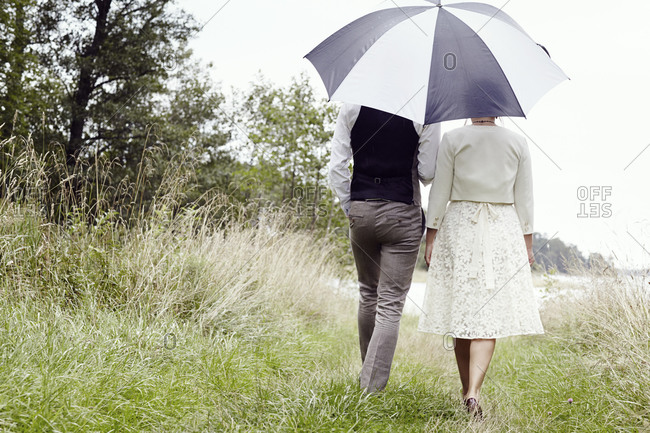 Rear view of a bride and groom walking