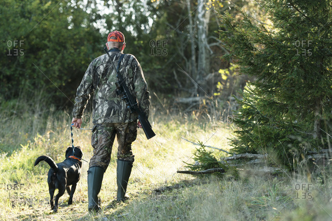 Rear view of man hunting with dog