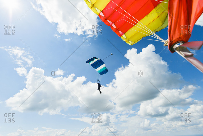 Sky-diver in air with open parachutes