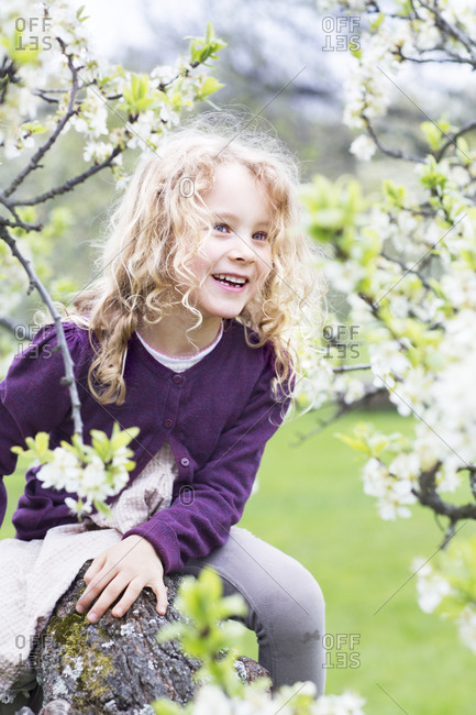 Smiling girl near blossoming tree