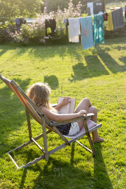 Teenage girl reading book in garden