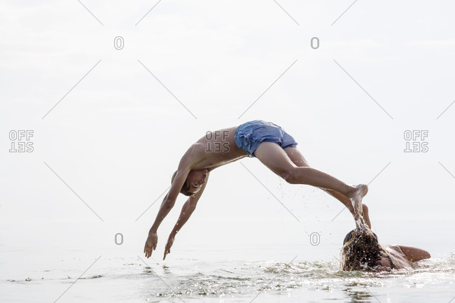 Teenager diving off another in a lake