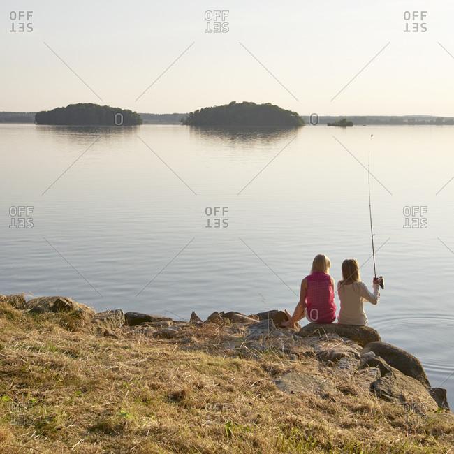Two sisters fishing at lake