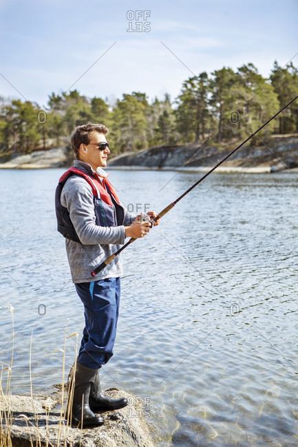 Profile of a young man fishing in wellingtons