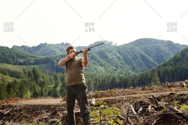 A man aims a shotgun in a field Man Aiming Shotgun in Field