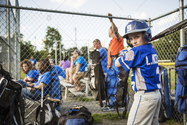 A youth leaguer practices his swings in the dugout