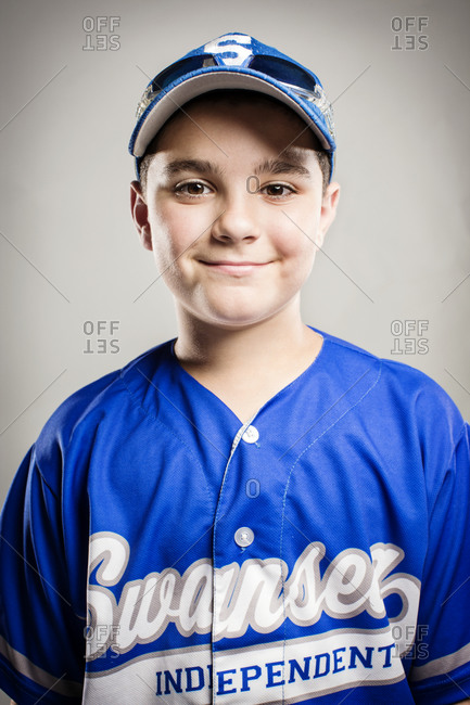 A youth leaguer in a blue uniform smiling