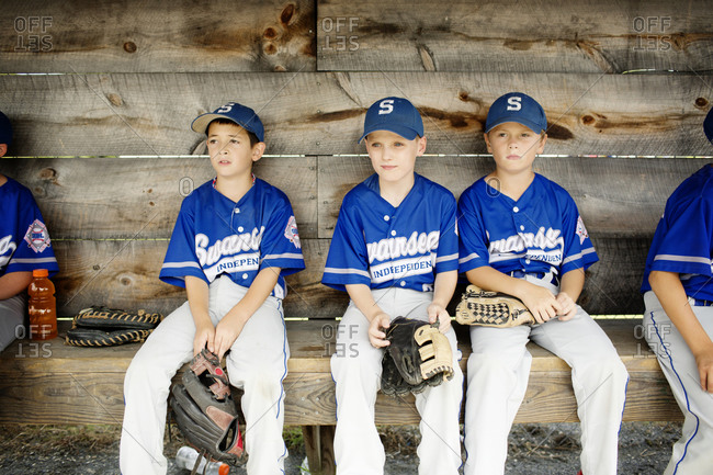 Youth league teammates sitting on a bench in a dugout