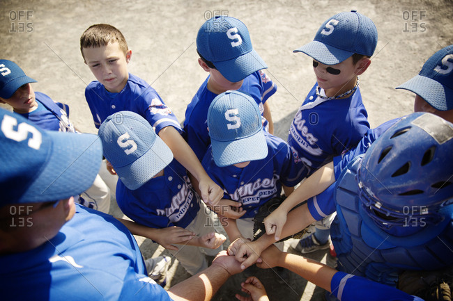 Little league players huddle together for encouragement