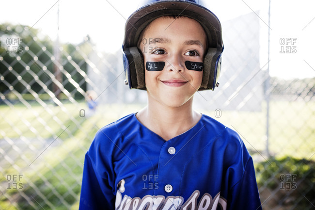 A youth league player in eye black smiles