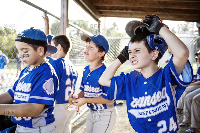 Youth leaguers grimace as they watch their teammates play
