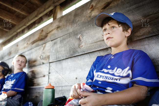 A youth leaguer watches the game from the game from the dugout