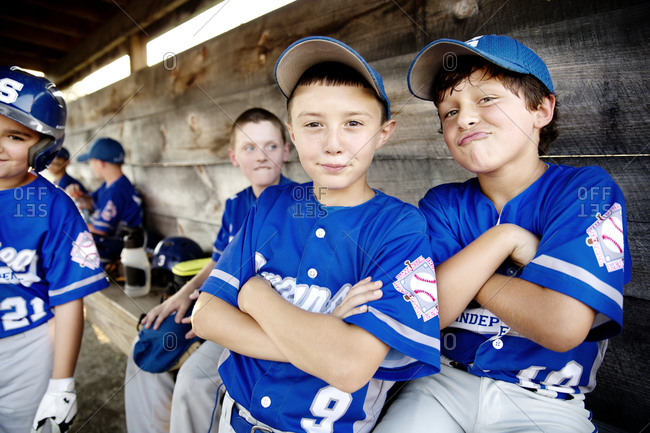 Youth league players goofing around in a dugout